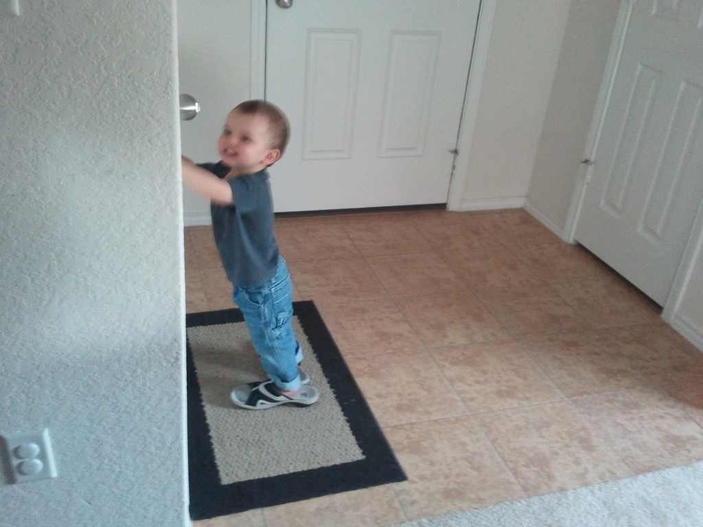 Seeing if Grandma's shoes make him tall enough to reach the door nob.