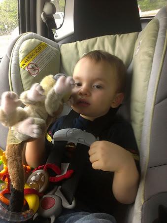 Tired boy with his souvenir monkey plush.