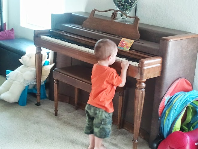 Pretending that he's playing music (the card is his sheet music...he put it up there and then started playing) :)